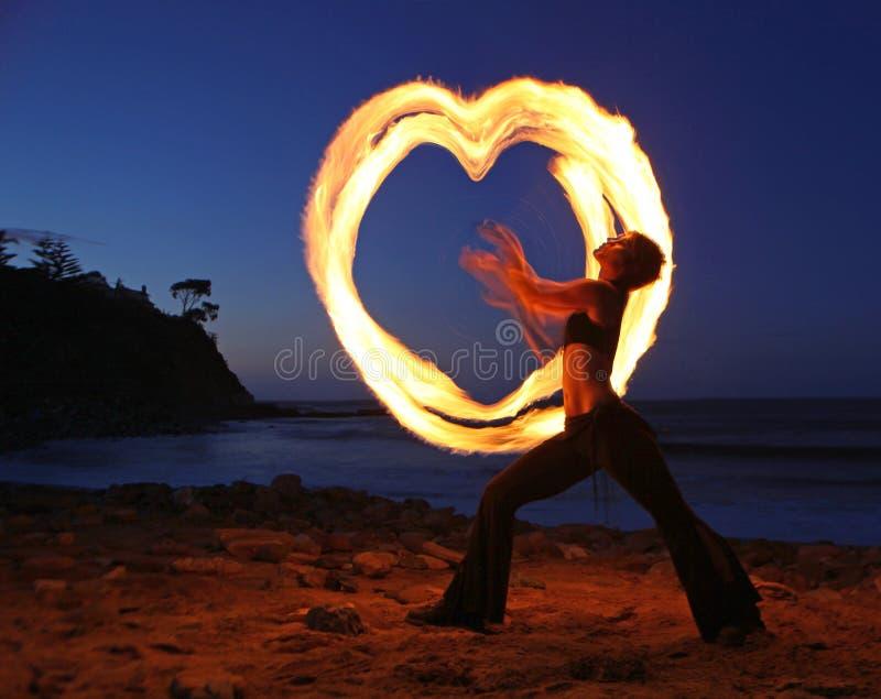 Firedancer ao longo da praia no crepúsculo. imagem de stock