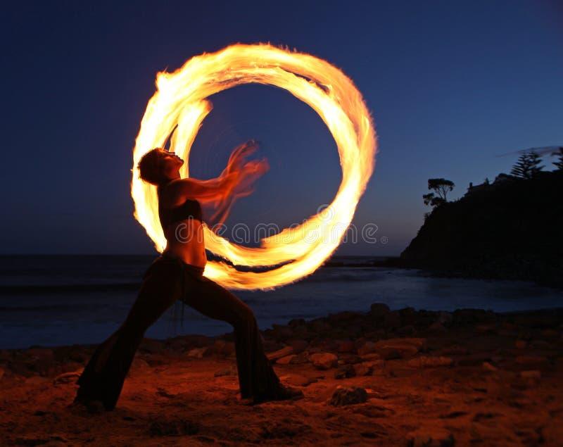 Firedancer le long de la plage au crépuscule. photographie stock libre de droits