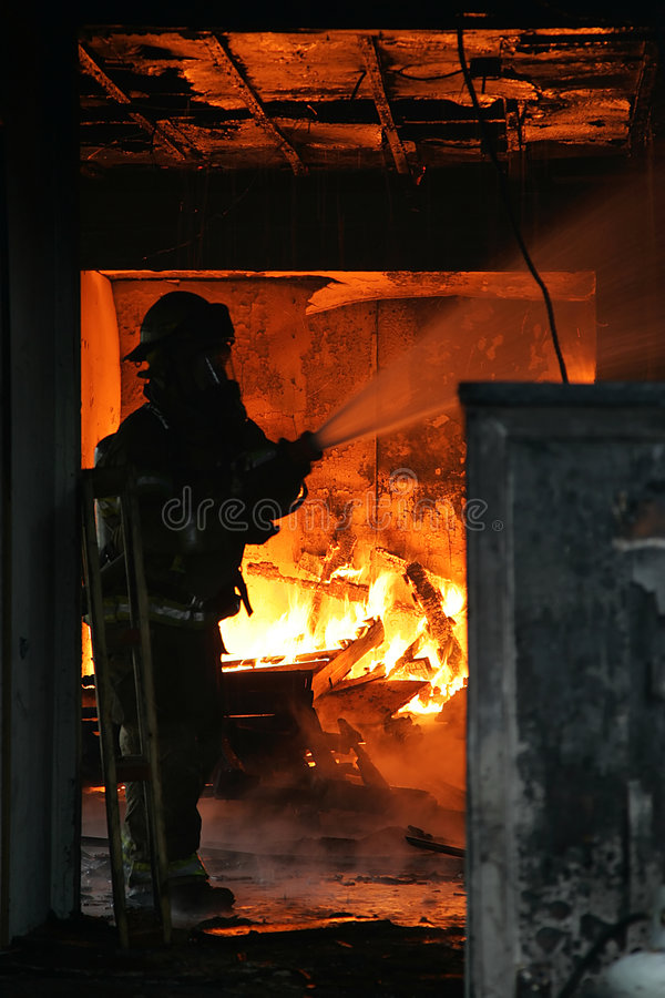 Firefighter. Fire fighter inside burning house royalty free stock image
