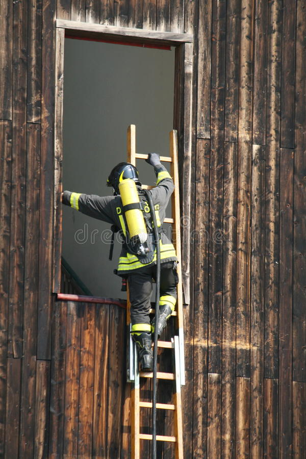 Firefighter in action enters through a window to rescue people stock image