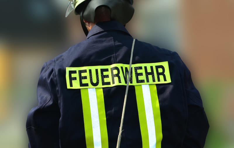 Firefighter from behind. Detail shot of a german firefighter from the rear with the inscription feuerwehr royalty free stock photo