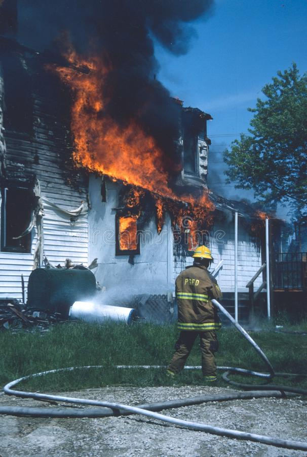 Firefighter cooling off oil tank outside a house stock photo