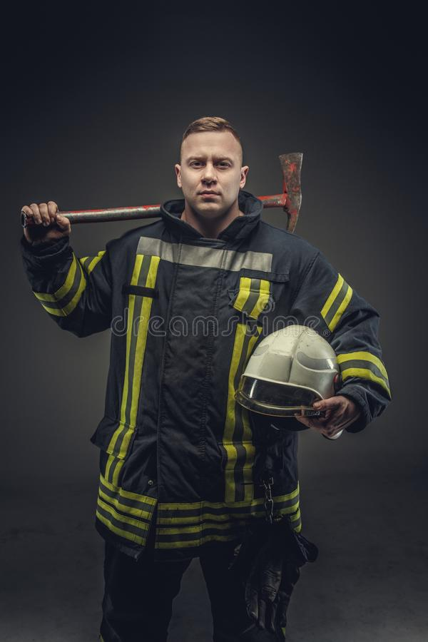 Firefighter costume holding helmet and recue red axe. royalty free stock photos