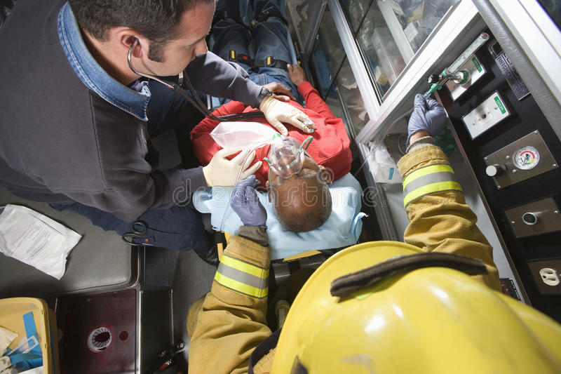 Firefighter And Doctor Taking Care Of Senior Man. Male firefighter and EMT doctor taking care of an injured senior men in ambulance stock photos