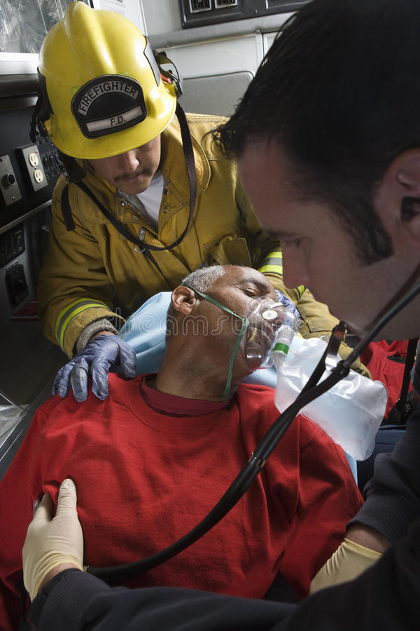 Firefighter And Doctor Taking Care Of Senior Man. Firefighter and EMT doctor taking care of an injured senior men in ambulance royalty free stock photo
