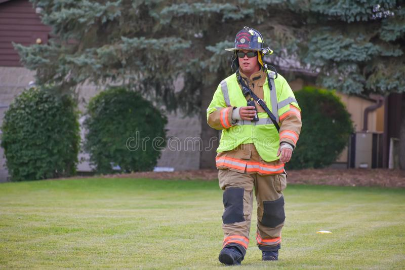 Firefighter Dressed in Full Gear. A Bloomfield Firefighter dressed in full gear walking through a grassy lawn royalty free stock images
