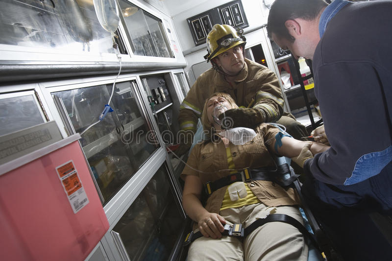Firefighter And EMT Doctor Helping An Injured Woman stock photo