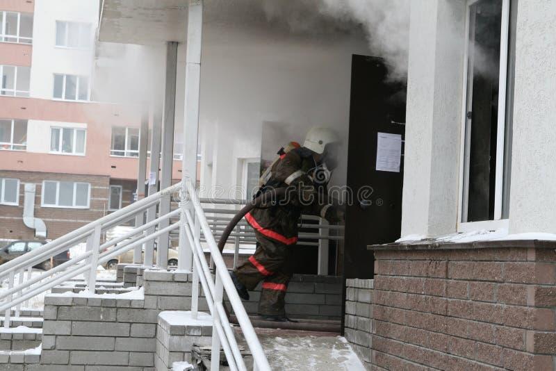 Firefighter enters to smoking door stock images