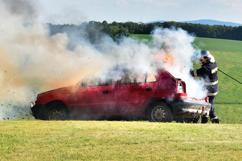 A firefighter extinguishes a car fire. Red car on fire, smoke and firefighter. Accident at the meadow.  royalty free stock image