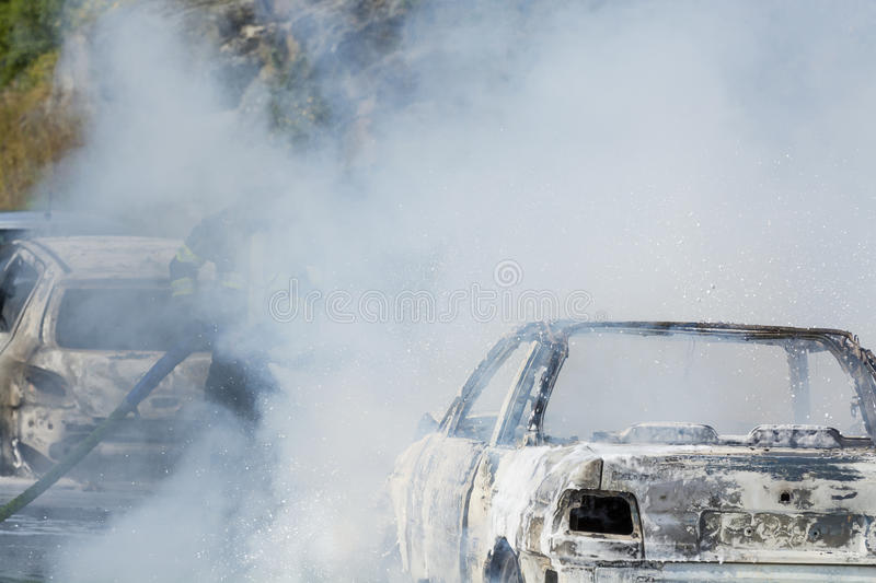 Firefighter extinguishes car fire. Firefighter in smoke extinguishes car fire with foam. Wearing breathing apparatus stock image