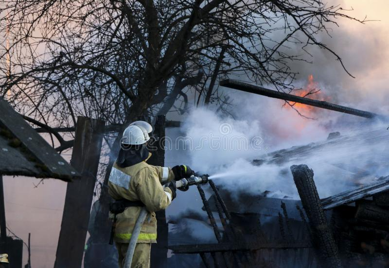 Firefighter extinguishes the fire. Fireman holding hose with water, watering strong stream of burning wooden structure in smoke. Firefighter extinguishes fire royalty free stock photo