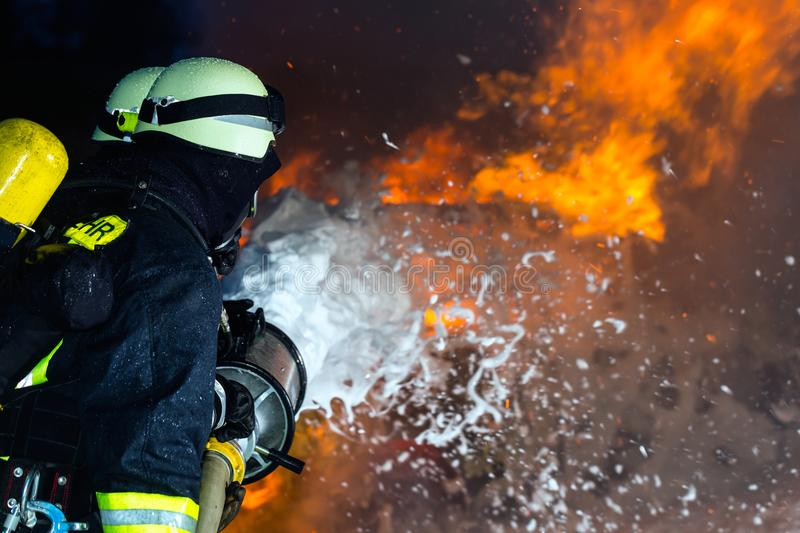 Firefighter - Firemen extinguishing a large blaze. They are standing with protective wear in front of wall of fire royalty free stock photography