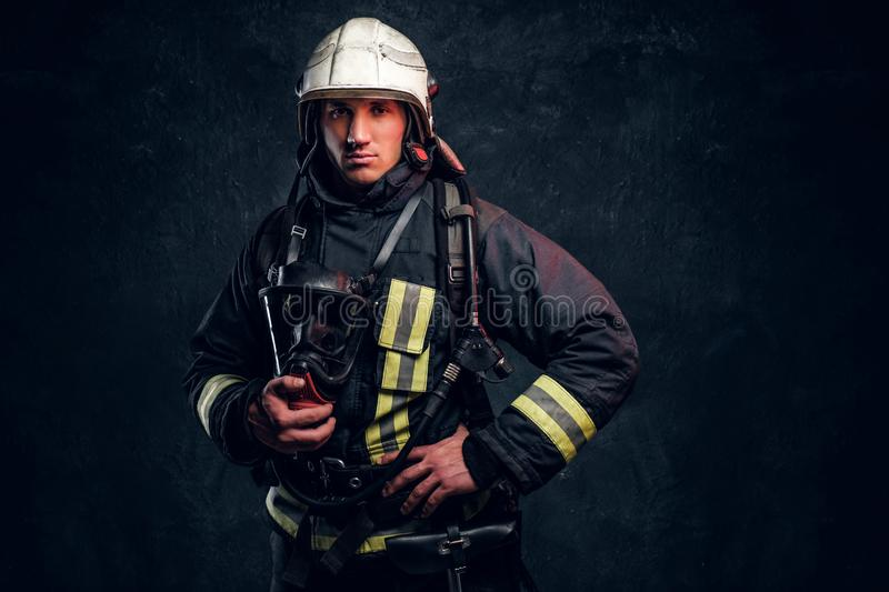 Firefighter in full protective equipment holding an oxygen mask and looking at a camera. Studio photo against a dark textured wall stock photos