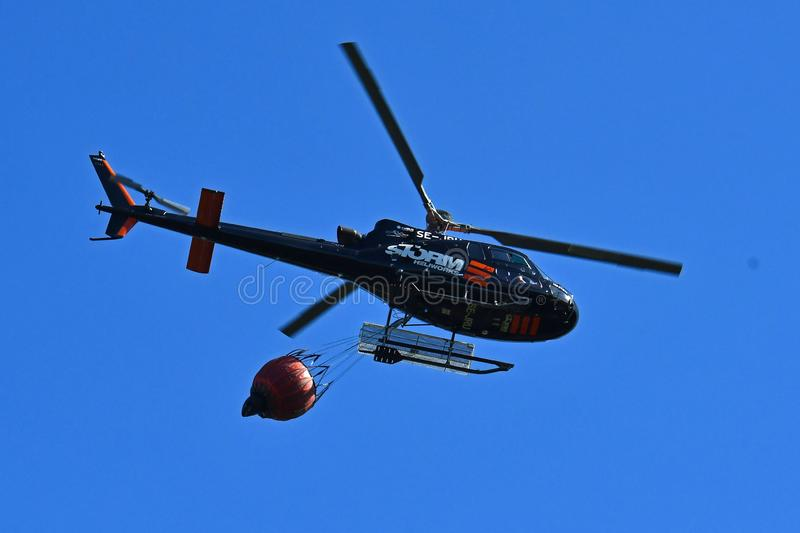 Firefighter helicopter during the rescue operation collects water in royalty free stock photos