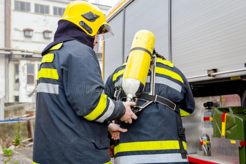 Fireman is helping colleague to manage full safety gear royalty free stock image