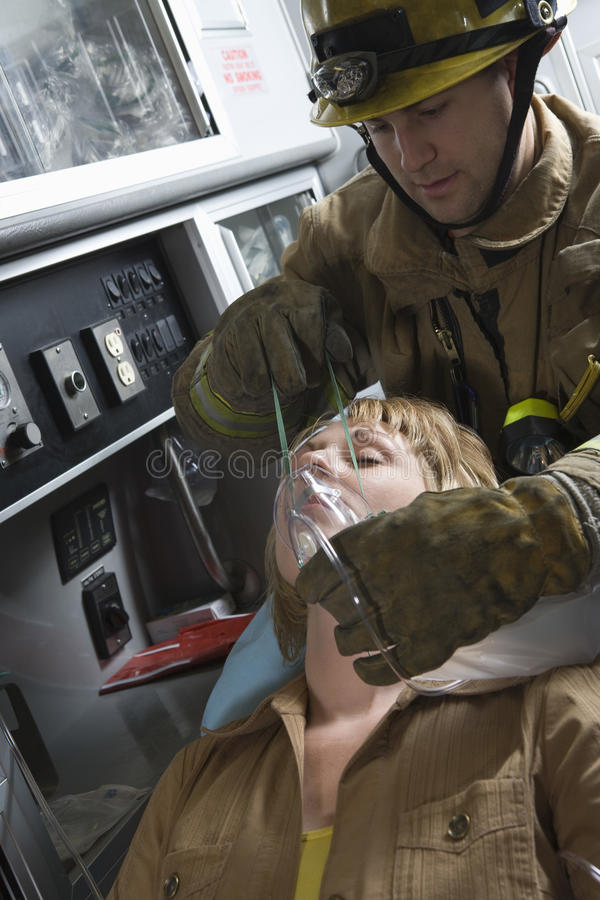 Firefighter Helping An Injured Woman royalty free stock image