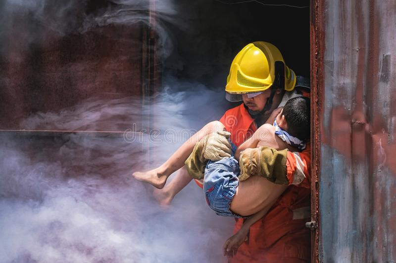 Firefighter holding child boy to save him in fire and smoke Firemen rescue the boys stock images