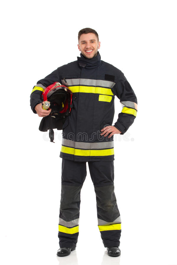 Firefighter holding helmet under his arm stock photo
