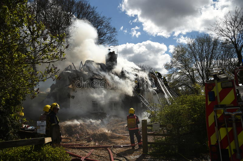 Firefighter hoses down a fire in a thatched cottage stock photo