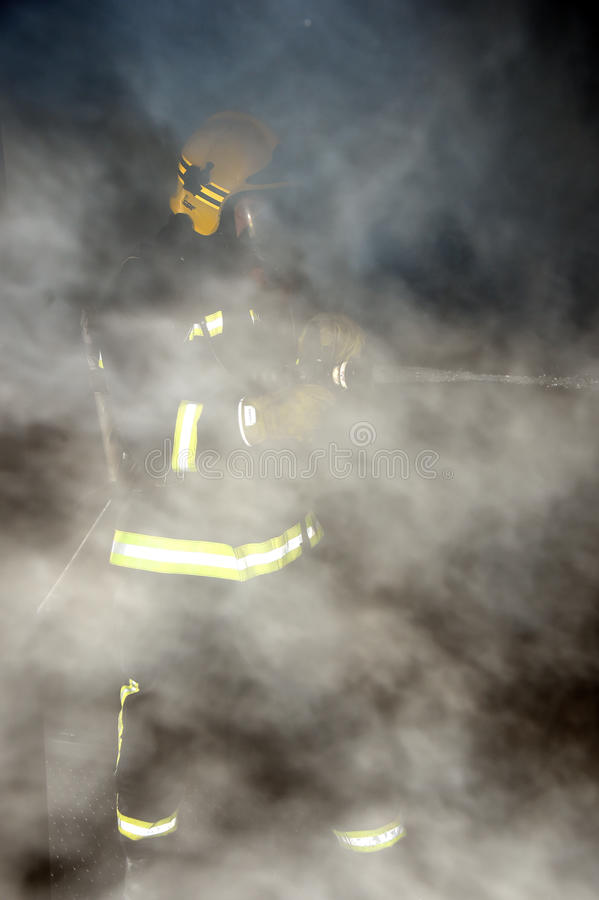 Firefighter hosing down and damping in a smoke filled building royalty free stock photography