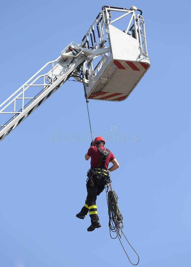 Firefighter hung the rope climbing in the firehouse. Firefighters hung the rope climbing during the practical exercise in firehouse royalty free stock images