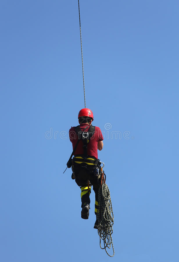Firefighter hung the rope climbing during the practical exercise. Climber firefighter hung the rope climbing during the practical exercise royalty free stock photo