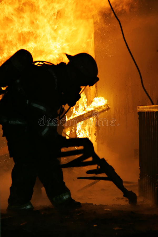 Firefighter Inside House. Firefighter removing debris out of way inside a house fire royalty free stock image