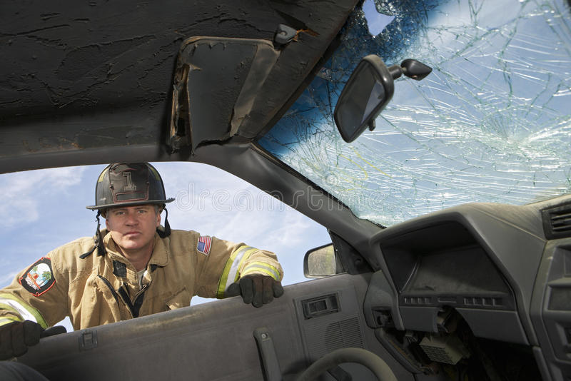 Firefighter Looking Into Crashed Car royalty free stock image
