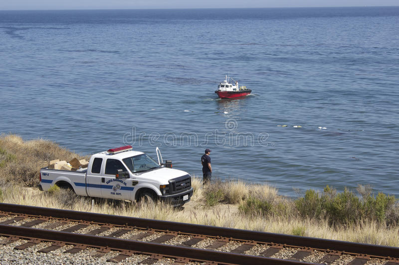 Firefighter observes oil spill cleaing efforts at Refugio State stock images
