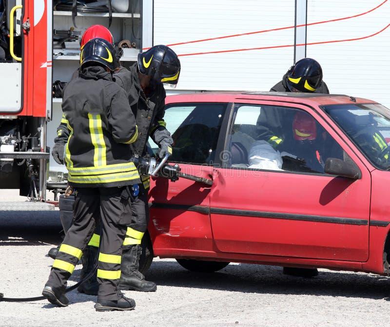 Firefighter opens car door with pneumatic shears after the road. Firefighter opens car door with pneumatic shears after the traffic accident stock image