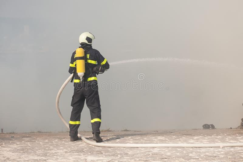 Firefighter in protective suit works with water hose. Fighting for a fire attack. Firefighter in protective suit works with water hose. Fighting for a fire royalty free stock photography