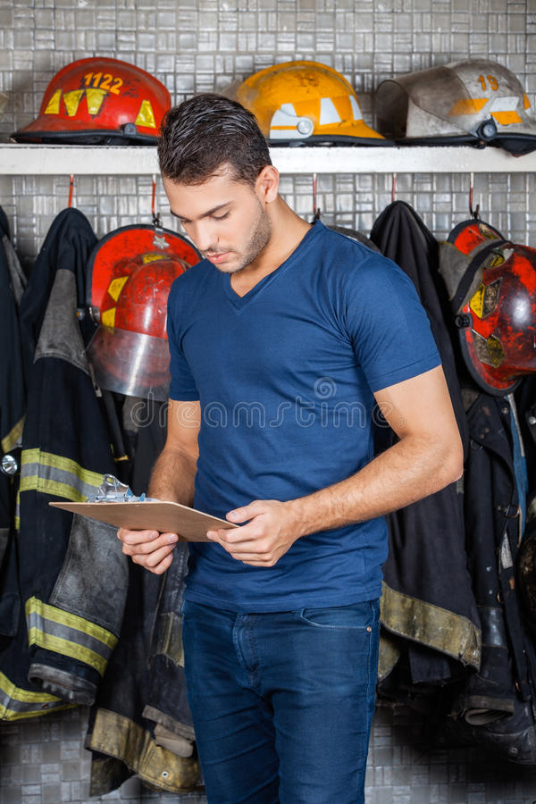 Firefighter Reading Clipboard At Fire Station. Firefighter reading clipboard against uniforms hanging at fire station royalty free stock photos
