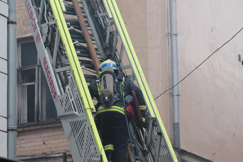 Firefighter rises on the fire ladders. The hearth fire stock images
