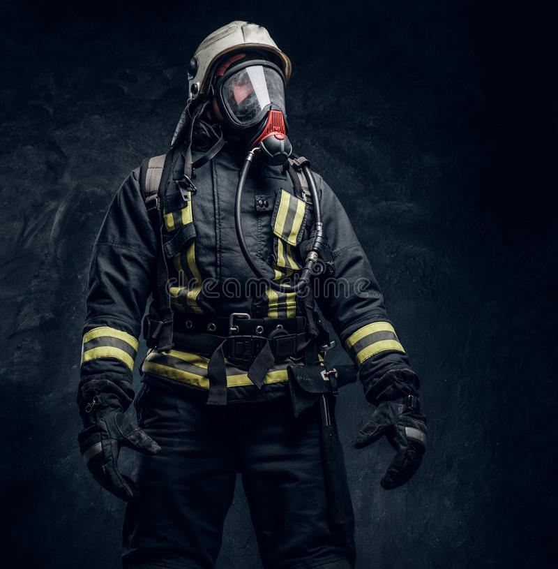 Firefighter in safety helmet and oxygen mask wearing protective clothes. stock images
