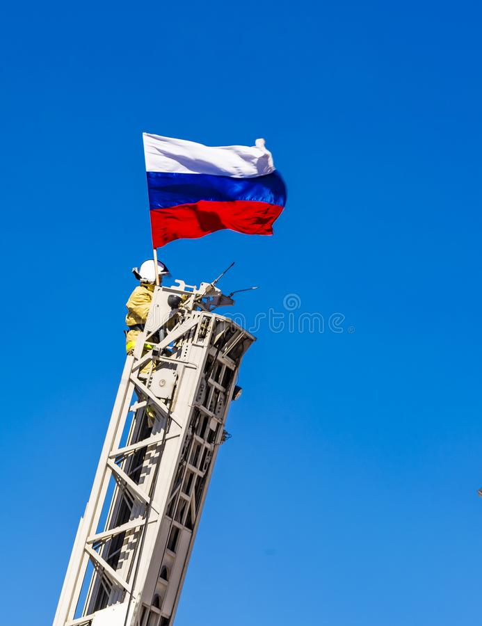 The firefighter secures a Russian flag on the fire ladder on background of blue sky stock image
