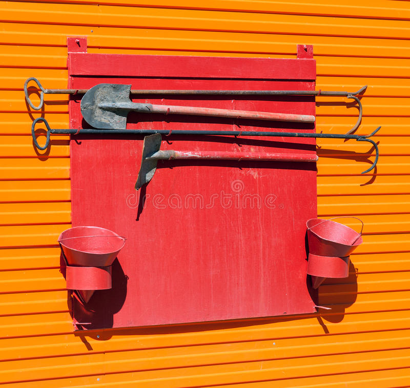 Firefighter shield. With fire extinguishing tools stock photography