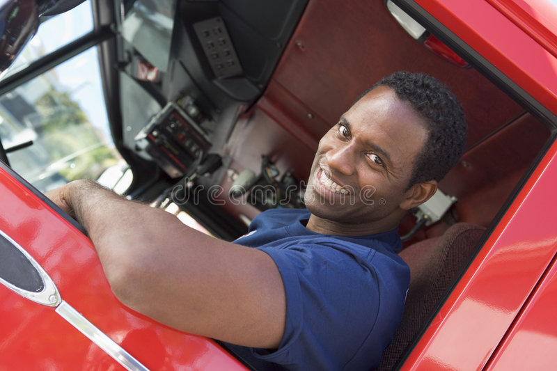 A firefighter sitting in the cab of a fire engine. Smiling royalty free stock photography