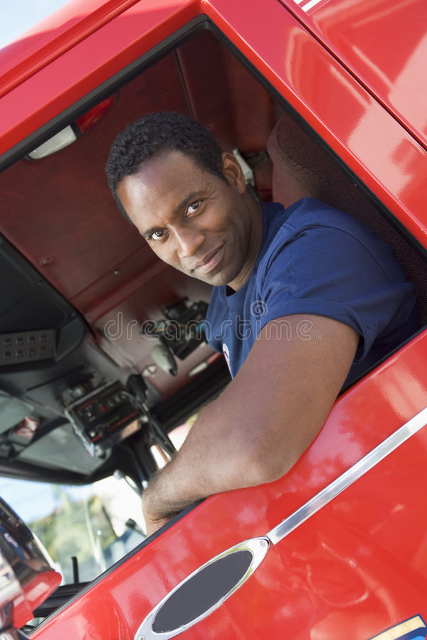 A firefighter sitting in the cab of a fire engine. Looking at camera royalty free stock images