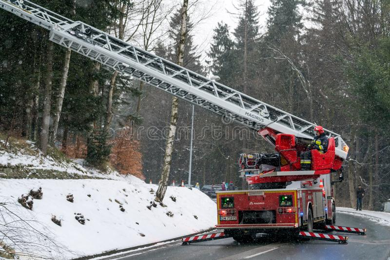 Fire engine on the road. Firefighter sitting in control chair operating an extendable crane arm with his colleagues in it cutting branches of a tree after heavy royalty free stock image