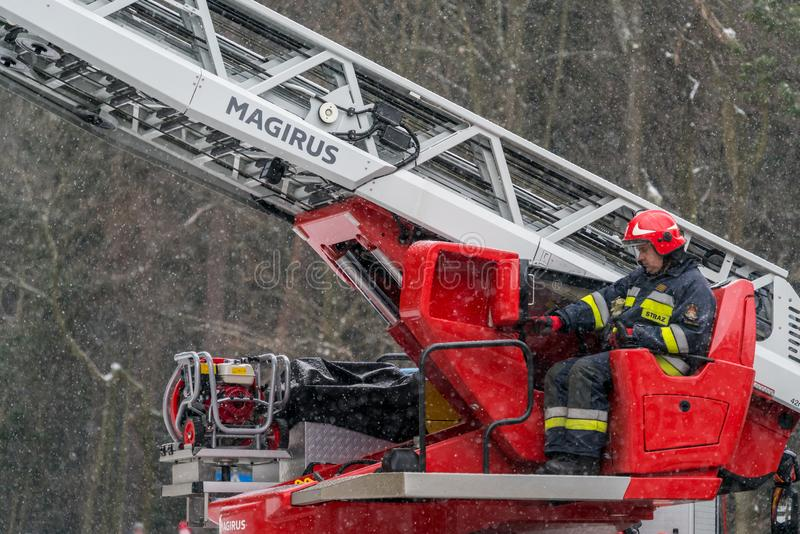 Firefighters operating crane arm stock image
