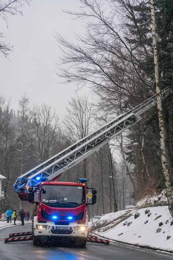 Fire engine on the road. Firefighter sitting in control chair operating an extendable crane arm with his colleagues in it cutting branches of a tree after heavy stock images