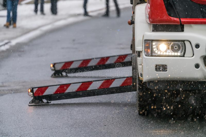 Fire engine on the road closeup. Firefighter sitting in control chair operating an extendable crane arm with his colleagues in it cutting branches of a tree royalty free stock images