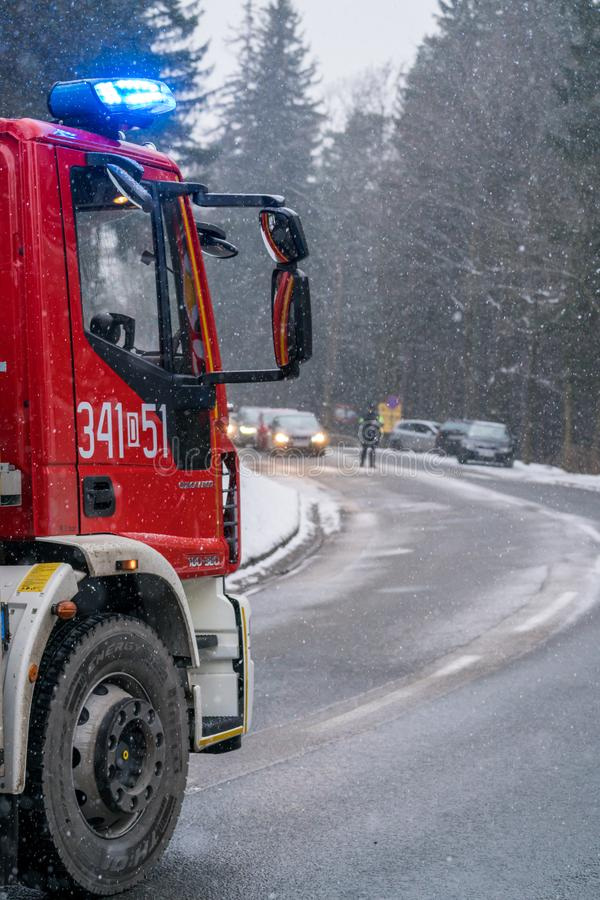Fire engine on the road closeup. Closeup of a fire engine cabin called in to clear the fallen branchech of pine trees after heavy snowfall in winter in Karpacz royalty free stock photos