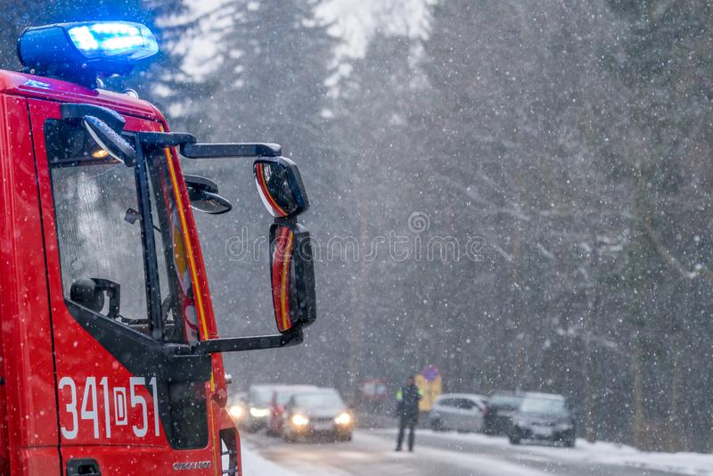 Fire engine on the road closeup. Closeup of a fire engine cabin called in to clear the fallen branchech of pine trees after heavy snowfall in winter in Karpacz stock photography