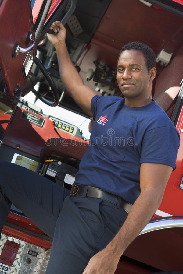 A firefighter standing by the cab of a fire engine. Looking at camera stock photo