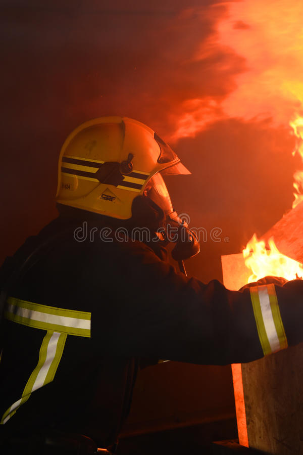 Firefighter tackles flames in a burning building. royalty free stock image