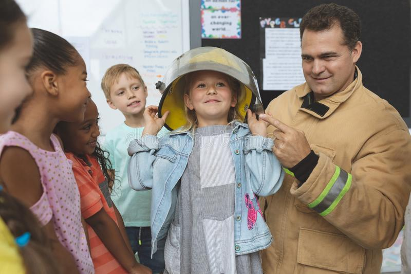 Firefighter teaching  fire safety to school kids at school. Front view of a Caucasian firefighter teaching to school kids about fire security while one of them royalty free stock images