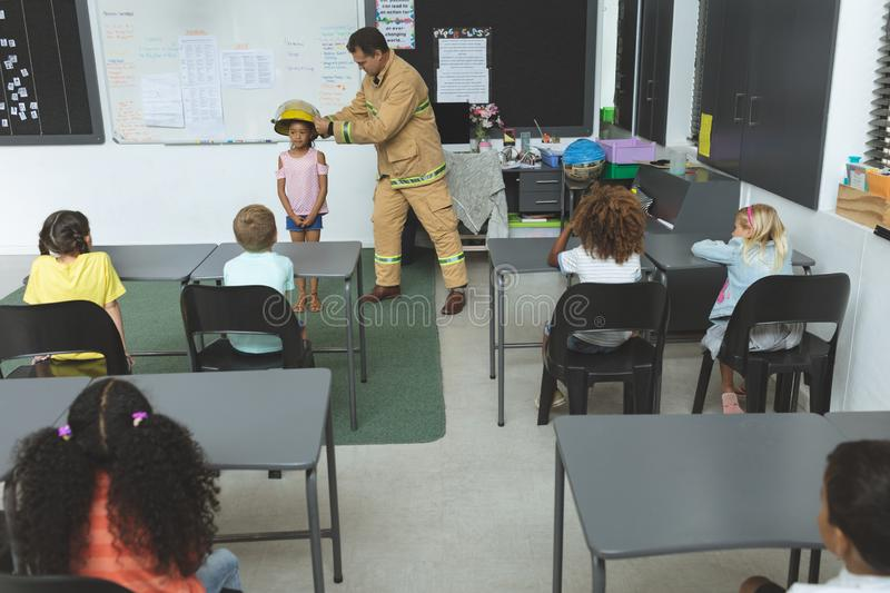 Firefighter teaching student about fire safety in classroom stock photos