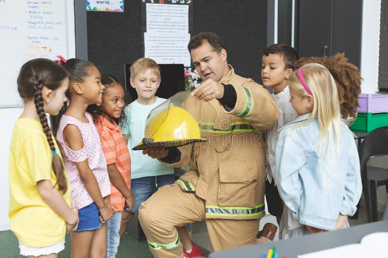 Firefighter teaching student about fire safety while holding fire helmet royalty free stock image
