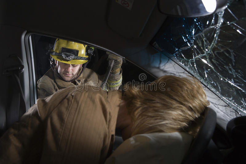 Firefighter Trying To Open Car's Door royalty free stock photography
